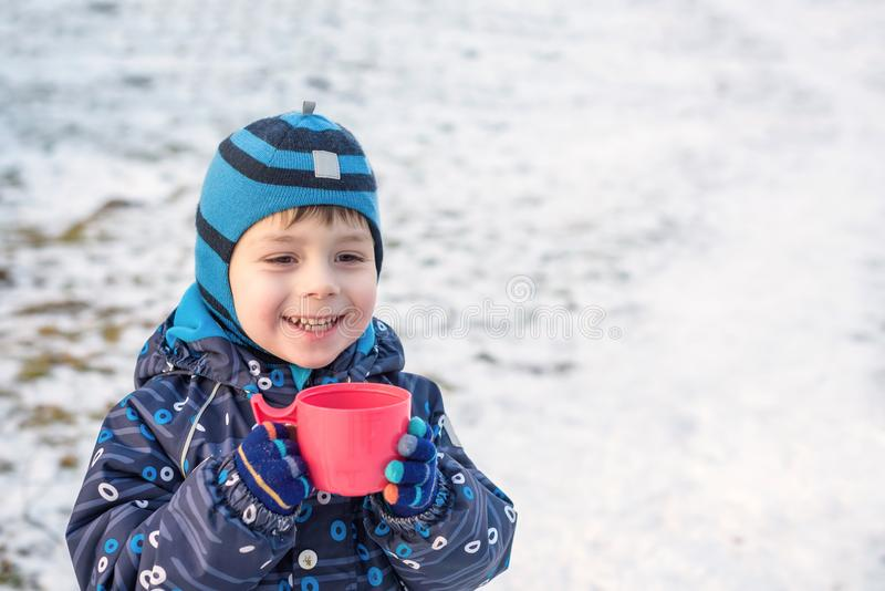 Little cute kid boy with cup of steaming hot chocolate or children punch. Happy child play in winter forest outdoors royalty free stock image