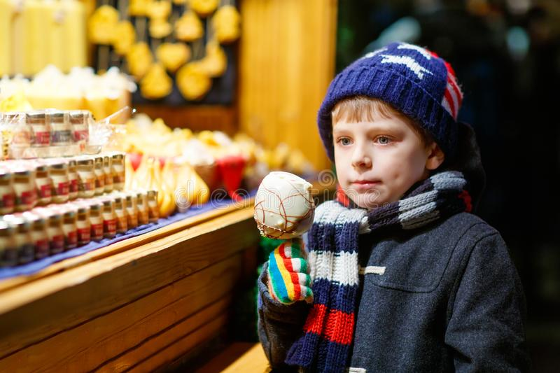 Little cute kid boy near sweet stand with gingerbread and nuts. Happy child eating on apple covered with white chocolate stock photography