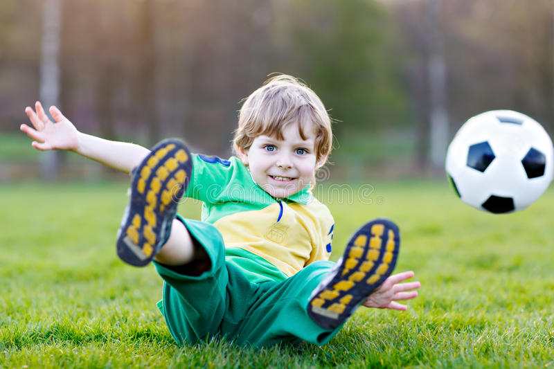 Little cute kid boy of 4 playing soccer with football on field, outdoors. Active child making sports with kids or father, Smiling happy preschool boy having stock photos