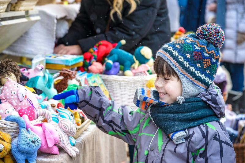 Little cute kid boy selecting decoration on Christmas market. Beautiful child shopping for toys and decorative ornaments. stock images