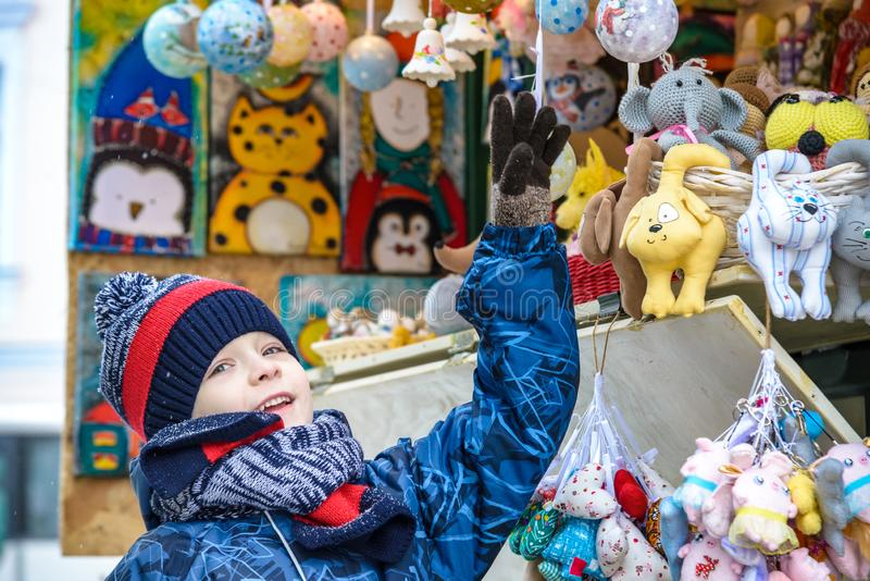 Little cute kid boy selecting decoration on Christmas market. Beautiful child shopping for toys and decorative ornaments. royalty free stock photography