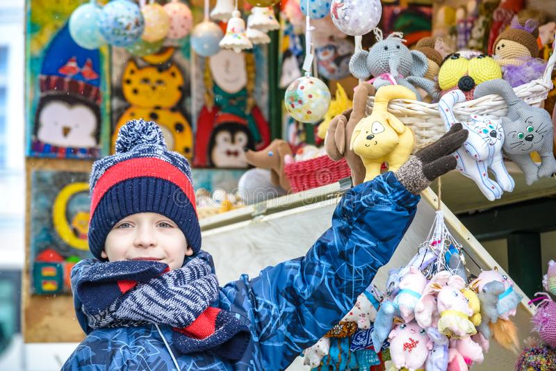 Little cute kid boy selecting decoration on Christmas market. Beautiful child shopping for toys and decorative ornaments. royalty free stock images