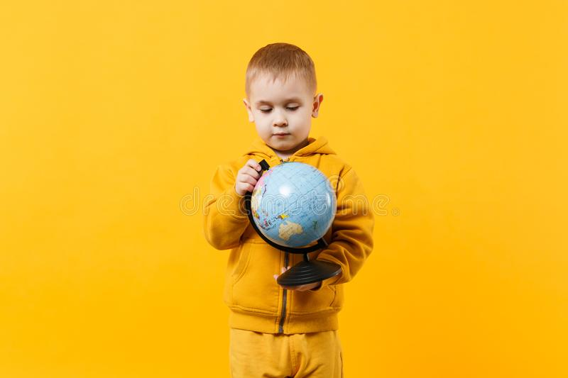 Little cute kid boy wearing yellow clothes hold Earth world globe isolated on orange wall background, children studio. Little cute kid boy wearing yellow clothes royalty free stock photography