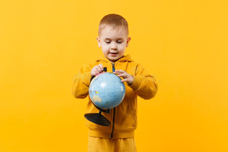 Little cute kid boy wearing yellow clothes hold Earth world globe isolated on orange wall background, children studio. Little cute kid boy wearing yellow clothes royalty free stock photos
