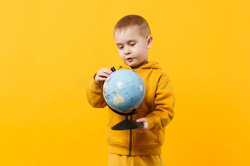 Little cute kid boy wearing yellow clothes hold Earth world globe isolated on orange wall background, children studio. Little cute kid boy wearing yellow clothes stock image