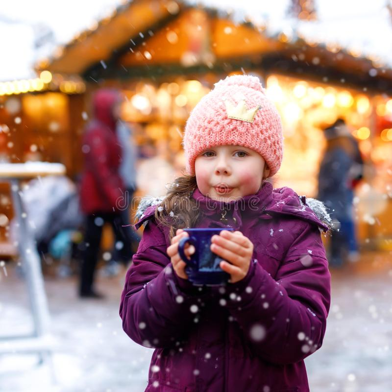 Little cute kid girl with cup of steaming hot chocolate or children punch. Happy child on Christmas market in Germany stock photos