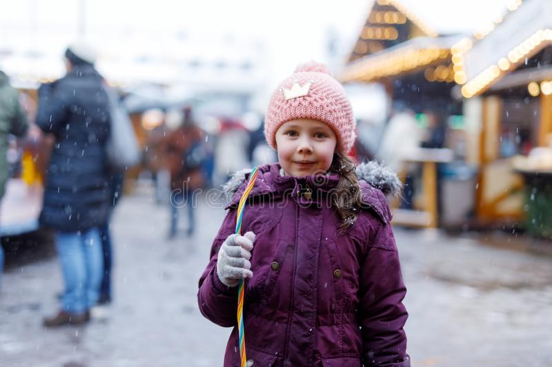 Little cute kid girl having fun on traditional German Christmas market during strong snowfall.. Happy child eating candy royalty free stock images