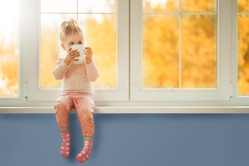 Little cute Kid Girl sitting by window holding cup of hot drink cocoa enjoying autumn forest background. Season Beauty fashion royalty free stock photos