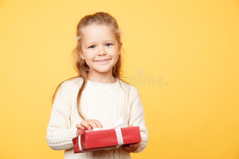 Little cute kid holding red present standing isolated in the yellow studio. stock photos