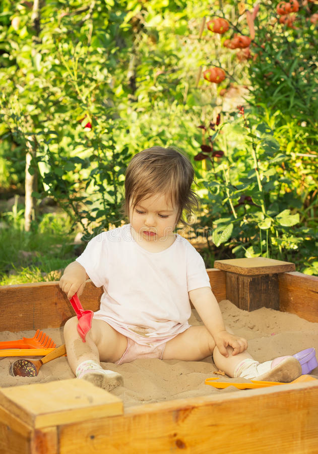 Little cute kid is playing in the sandbox on the playground royalty free stock photo