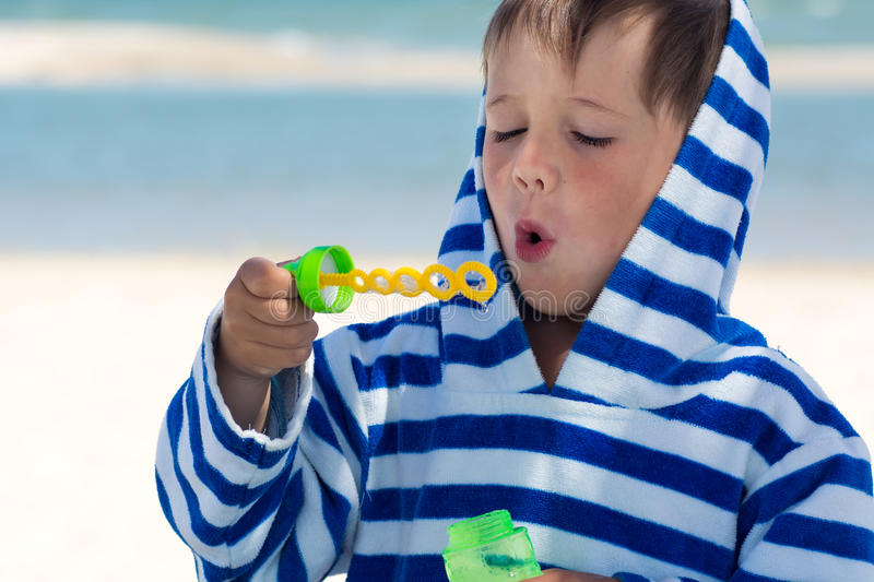 A little cute kid in a striped robe blows soap bubbles against the background of the sea and the washed braid. Baby gets air royalty free stock images