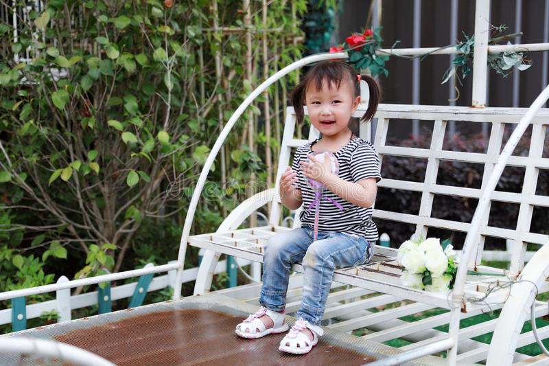 Little cute lovely girl Chinese child smile and play sit on a white benches hold a lollipop and flower at summer park nature royalty free stock photography