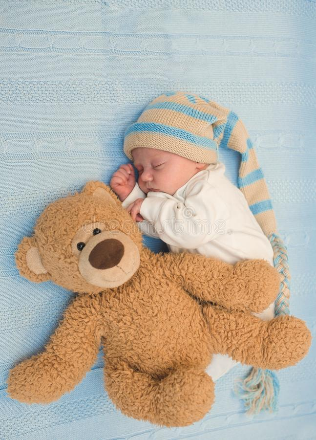 Newborn baby laying with teddy bear on blanket stock photos
