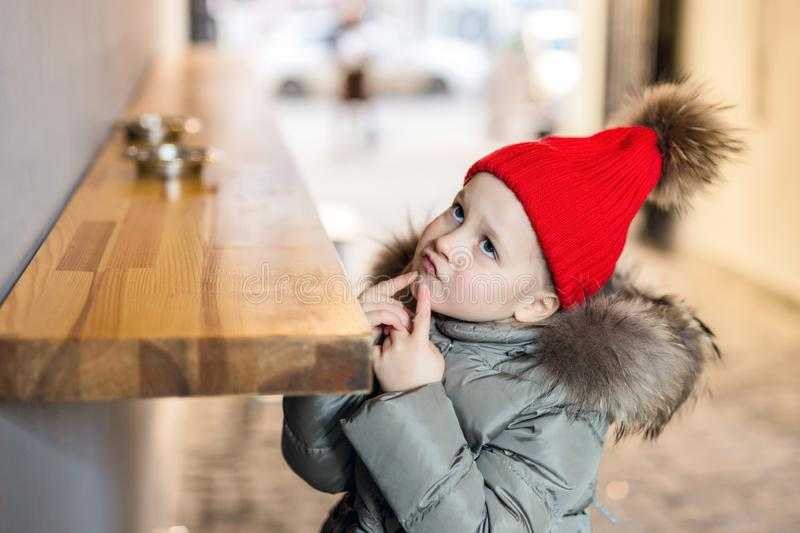 Little cute pensive caucasian girl in red knitted hat and warm jacket sitting at counter outdoors and thinking or dreaming about. Something and looking royalty free stock images