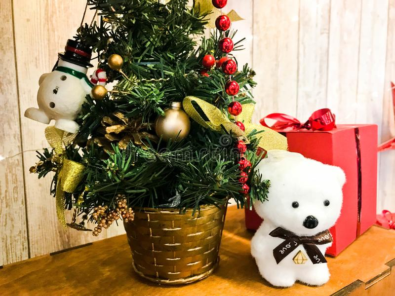 Little cute polar bear under the New Year`s elegant beautiful Christmas tree. New Year`s holiday decoration and gift red box stock photos