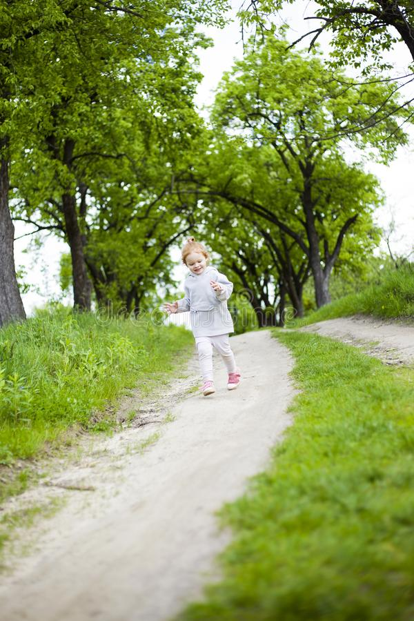 Little cute redhead girl runs along a dirt road with grass and laughs stock photo