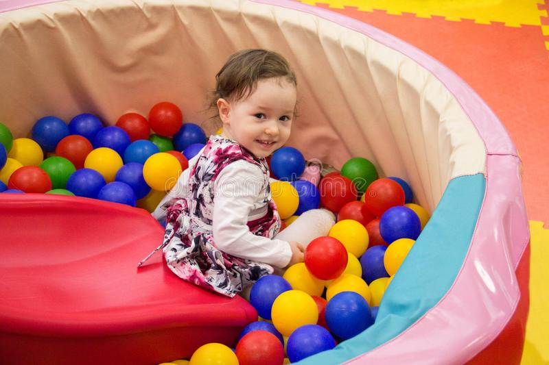 Little cute smile girl plays in balls for a dry pool. Play room. Happiness stock photos