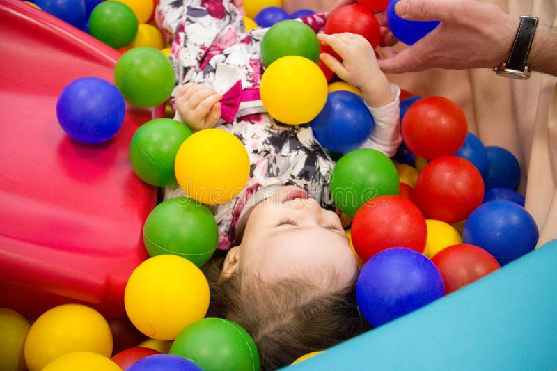 Little cute smile girl plays in balls for a dry pool. Play room. Happiness. father`s hand in the background royalty free stock photo