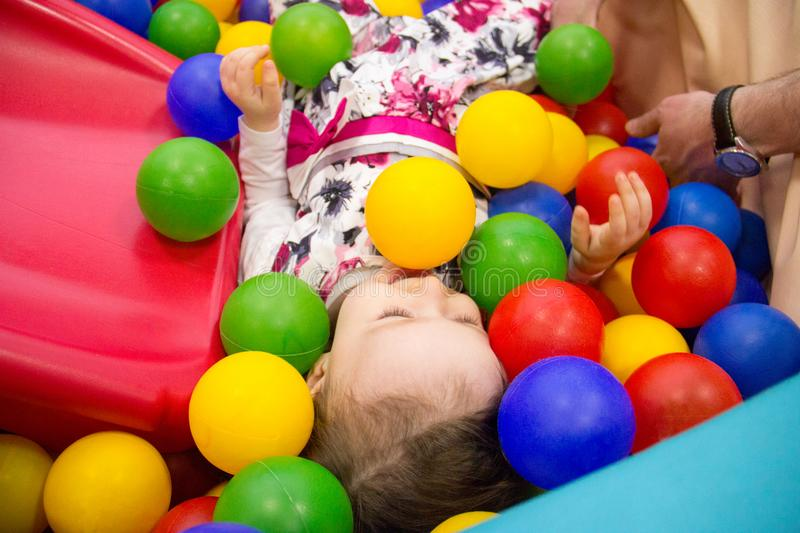 Little cute smile girl plays in balls for a dry pool. Play room. Happiness. father`s hand in the background stock image