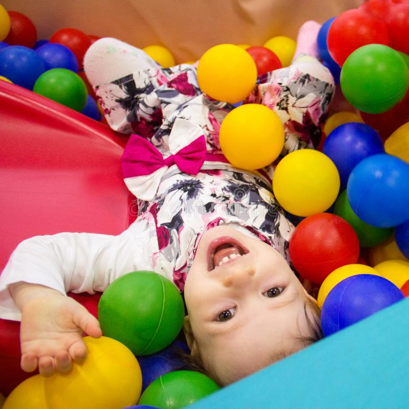 Little cute smile girl plays in balls for a dry pool. Play room. Happiness stock images