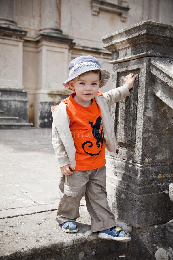 A little cute smiling boy in an orange t-shirt and a blue hat stands on an old staircase. The vertical frame. royalty free stock images