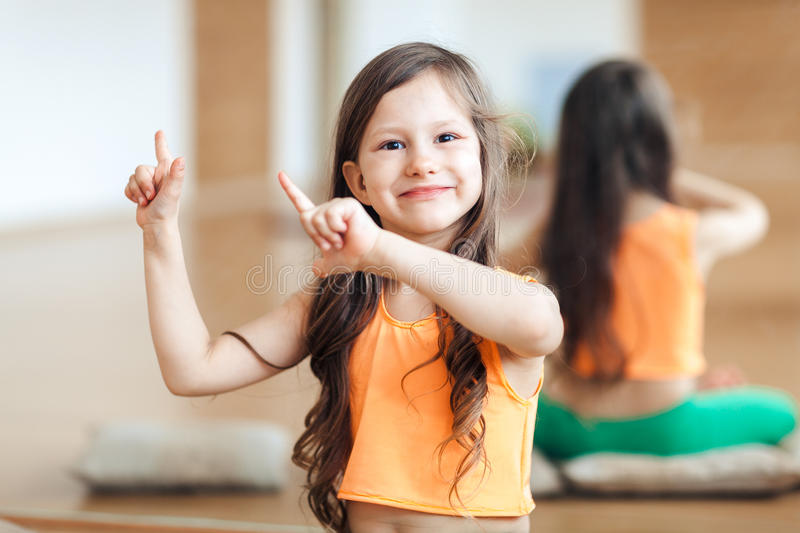 Little cute smiling girl in sportswear posing on camera in orange top, dancing, showing movements with hands stock photography