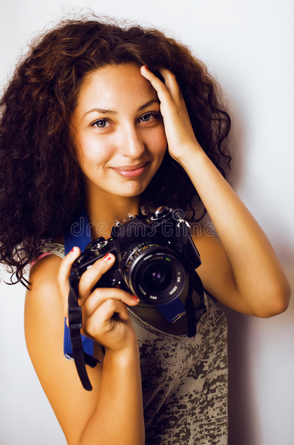 Little cute teenage girl with curly hair holding camera, photographer taking a shot, lifestyle people concept stock photo