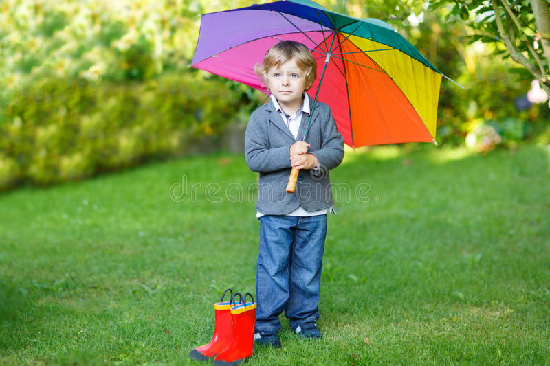Little cute toddler boy with colorful umbrella and boots, outdoors stock images