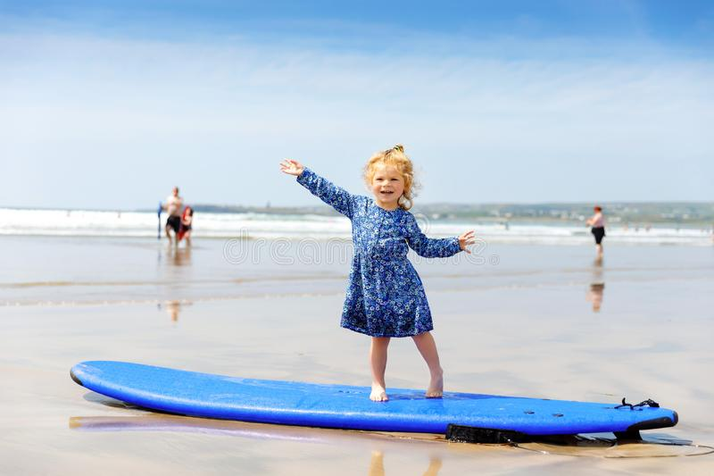 Little cute toddler girl at the Ballybunion surfer beach, having fun on surfboard for the first time, west coast of. Little cute toddler girl at the Ballybunion royalty free stock photography