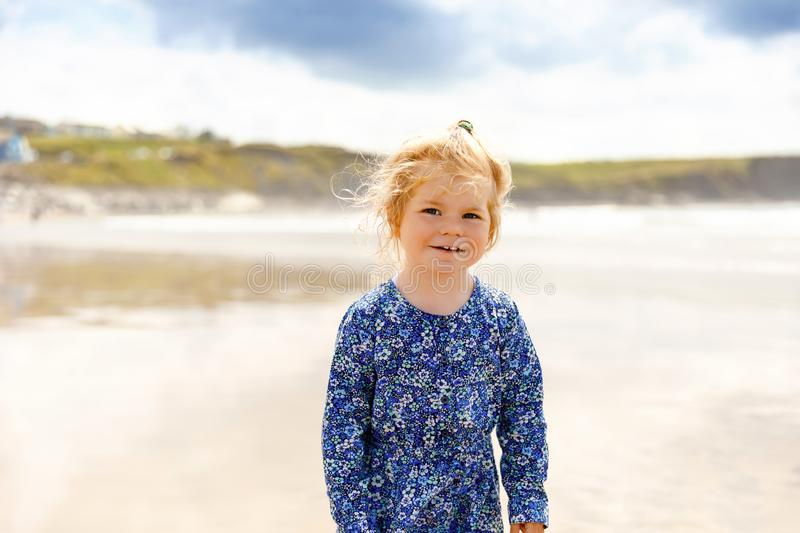 Little cute toddler girl at the Ballybunion surfer beach, having fun on surfboard for the first time, west coast of. Little cute toddler girl at the Ballybunion stock photography