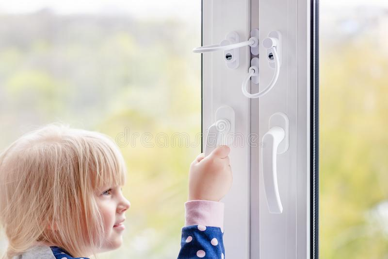 Little cute toddler girl trying to open window in apartment at high-tower building. Children window protection lock. Cable safety stock image