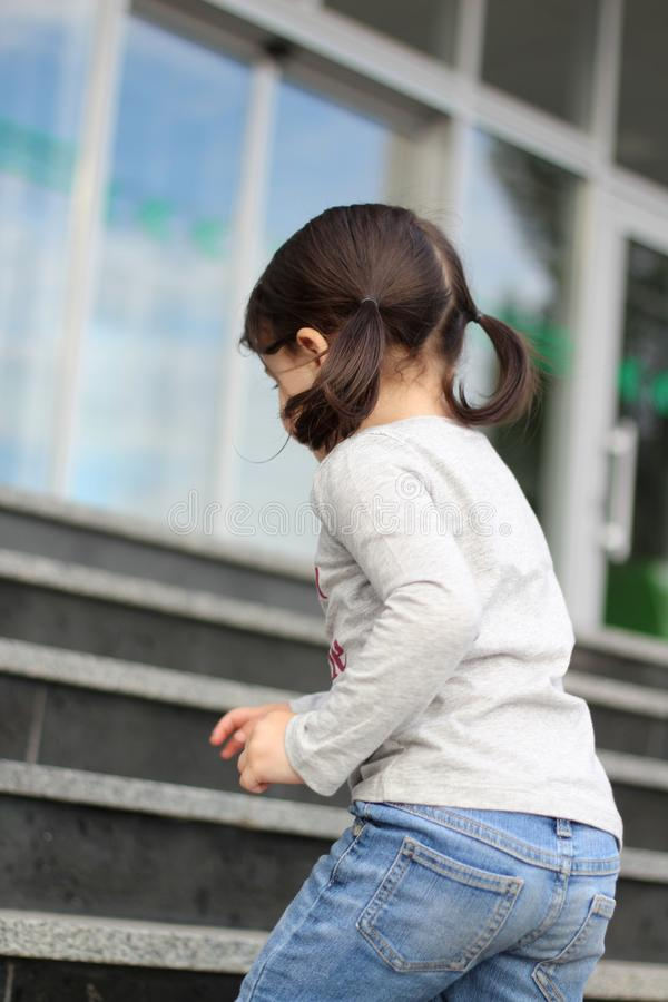 little cute white brunette girl with ponytails climbs up the stairs stock photography