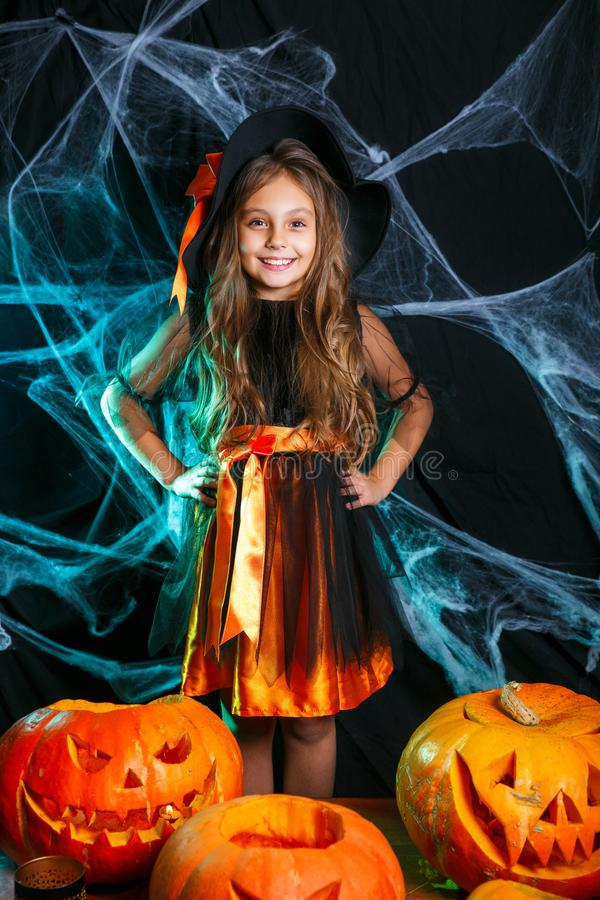 Little cute witch child having fun over spider web and with curved pumpkins background. Happy Halloween. Happy Halloween. Little witch child having fun over royalty free stock image