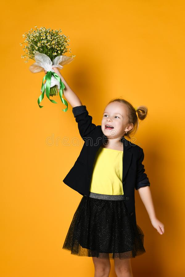 Little cute 5-year-old girl holds a large bouquet of daisies royalty free stock photography