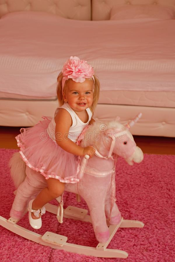 Little cutie. Small blond girl ride toy horse. Small child wear hair band. Little girl with long hairstyle. Hair royalty free stock images