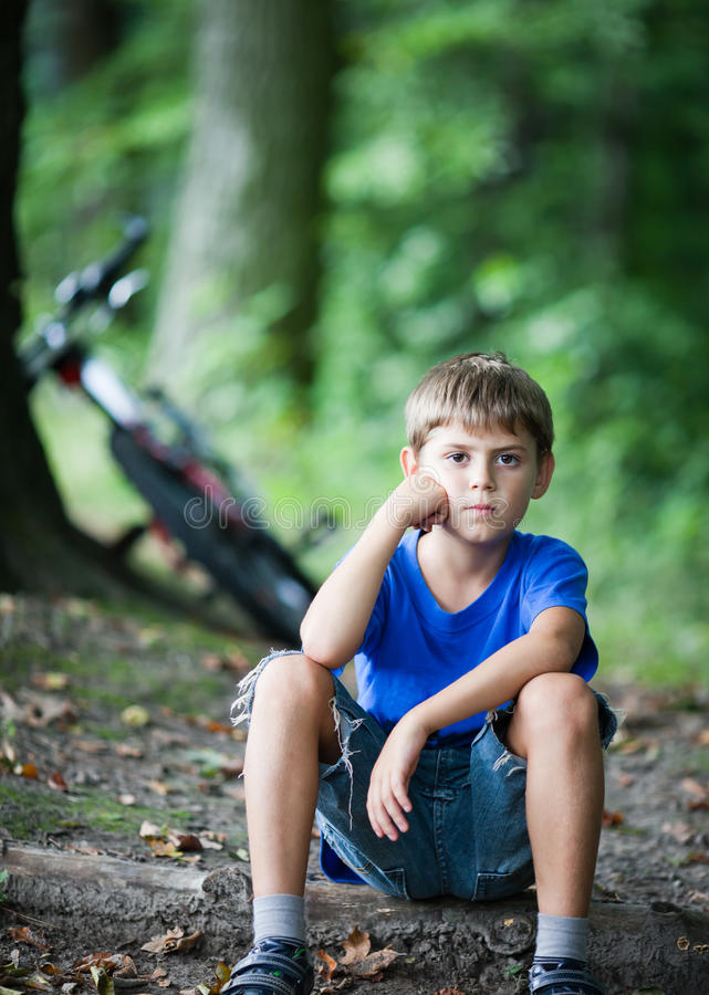 Little cyclist resting. Little cyclist while resting in the woods. Bicycle near a tree on background stock images