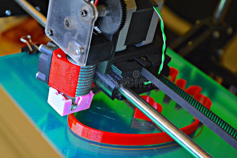 Little 3D Printing Machine printing a piece of red plastic. Working 3d printer. Little 3D Printing Machine printing a piece of red plastic royalty free stock image