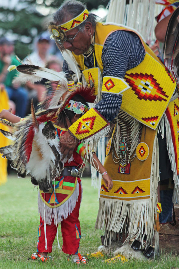 The Little Dancer - Powwow 2013. A grandfather helps his grandson get ready for dancing during the powwow in Indian Village, Cheyenne Frontier Days, 2013 royalty free stock photo