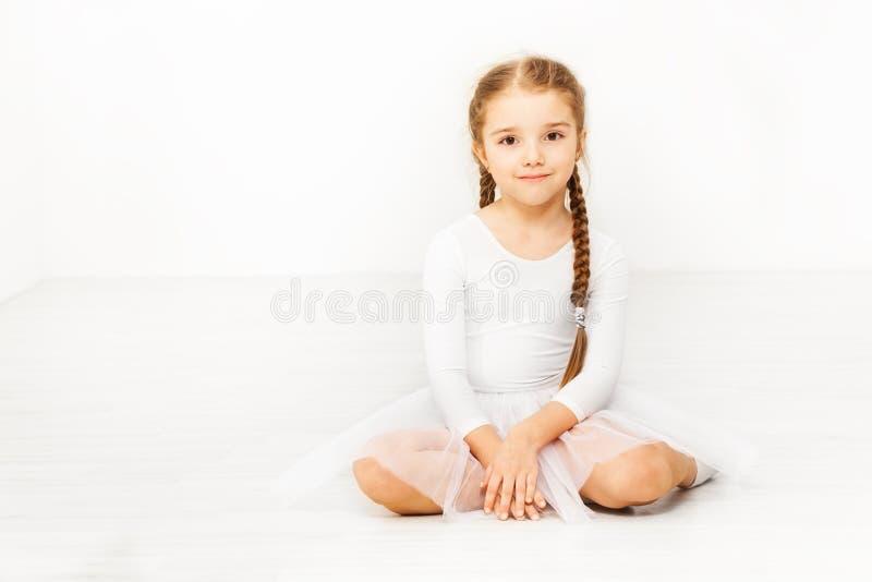 Little dancer sitting on floor of ballet studio. Portrait of Caucasian girl wearing white dancewear sitting on the floor of ballet studio with blanked background royalty free stock images