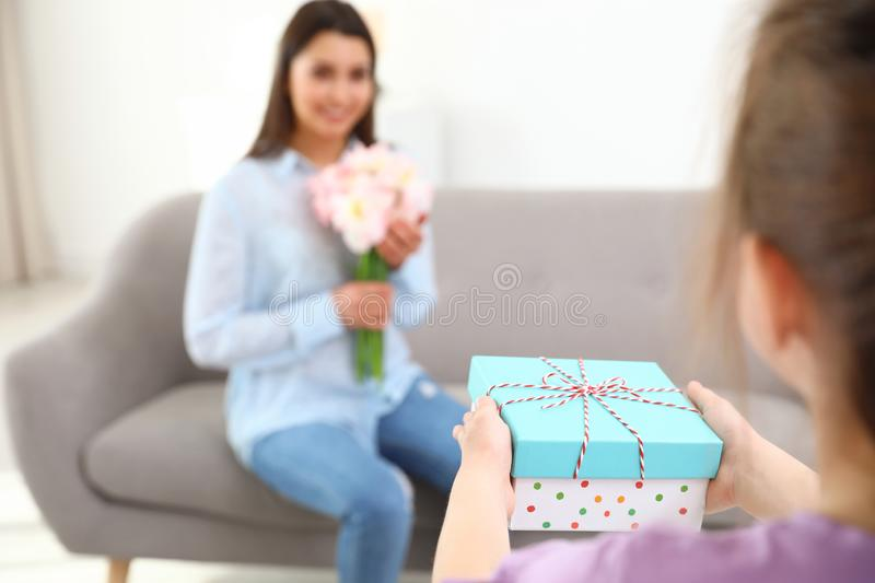 Little daughter congratulating her mom at home. Happy Mother`s Day royalty free stock image