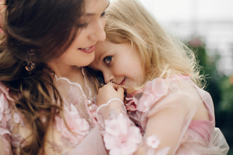 Little daughter cuddles up to her mom and smiles. stock image