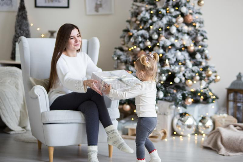 Little daughter gives mom a gift near the Christmas tree. White festive home interior royalty free stock photography
