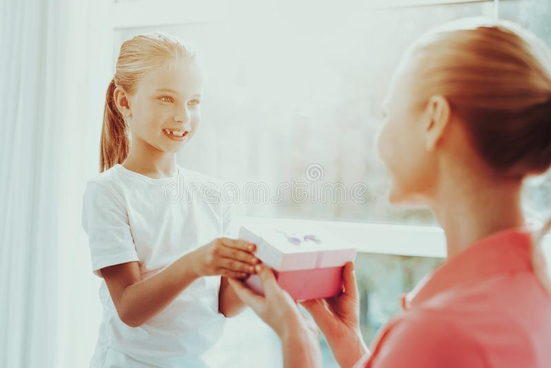 Little Daughter Is Giving A Present Box To Mum. Family Relationship Concept. Active Holiday. Beautiful Moment. Surprise To Parent. Happy Childhood. Celebrating stock images