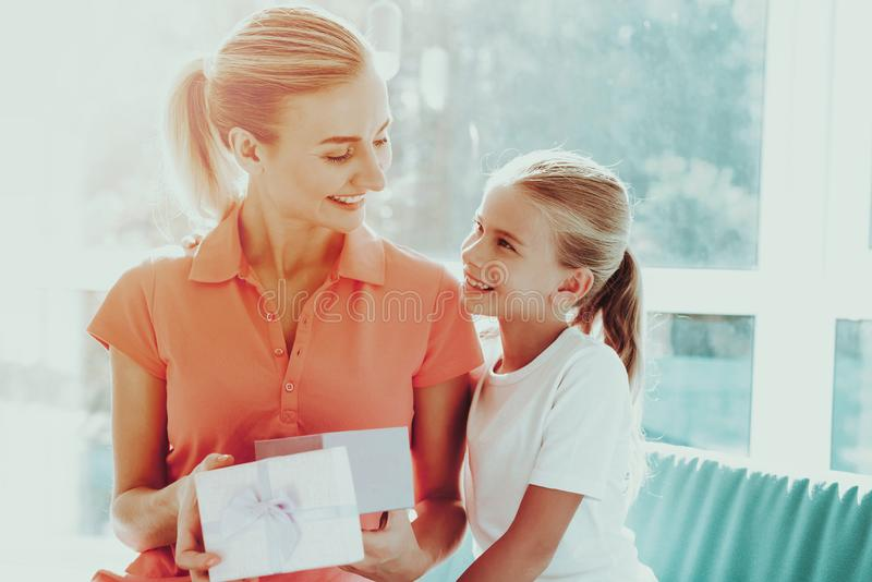 Little Daughter Is Giving A Present Box To Mum. Family Relationship Concept. Active Holiday. Beautiful Moment. Postcard To Parent. Happy Childhood. Celebrating royalty free stock photo
