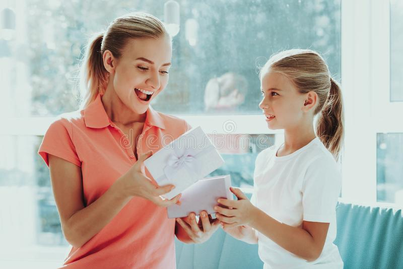Little Daughter Is Giving A Present Box To Mum. Family Relationship Concept. Active Holiday. Beautiful Moment. Postcard To Parent. Happy Childhood. Celebrating stock photos