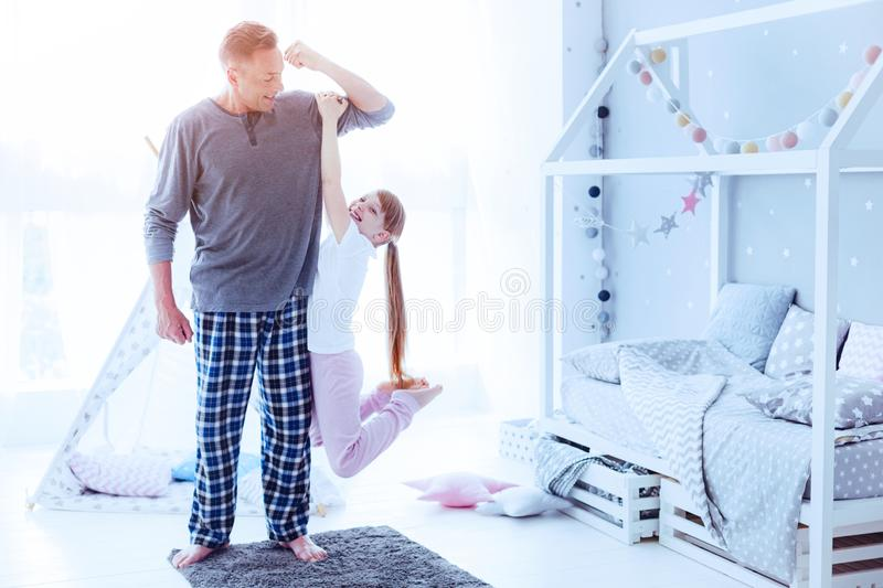 Little daughter hanging on fathers arm. Always ready to protect. Strong mature men smiling while showing his strength while his preteen daughter hanging on his royalty free stock images