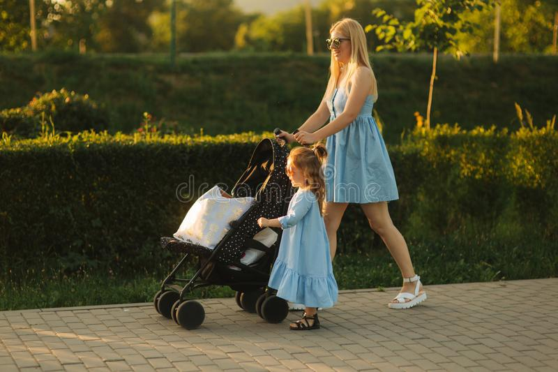 Little daughter helps mom push the baby carriage. Happy family royalty free stock image