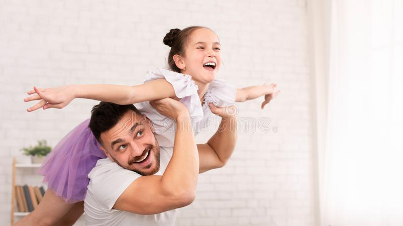 Little daughter and her handsome young dad flying like plane stock images