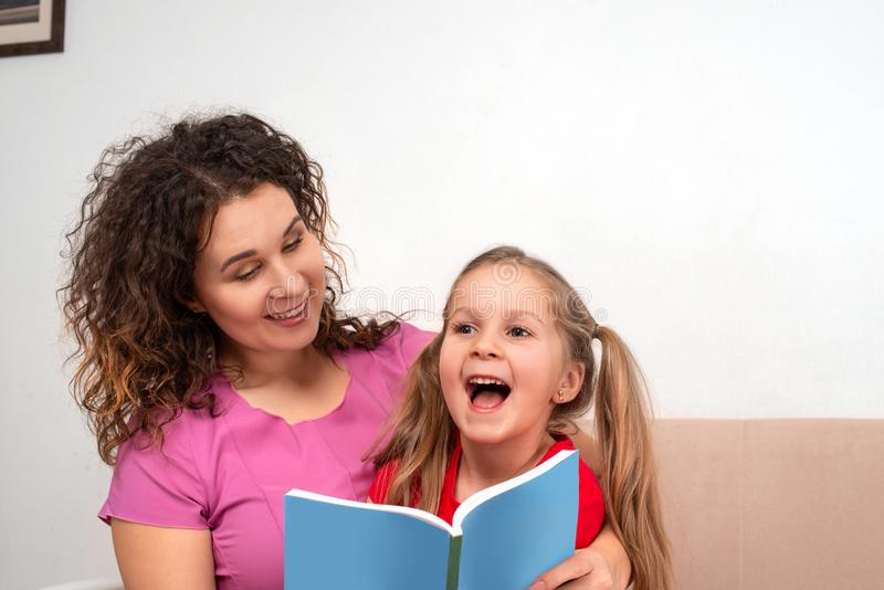 An little daughter and her mother spending time together. They sit on the couch and read a book stock photography