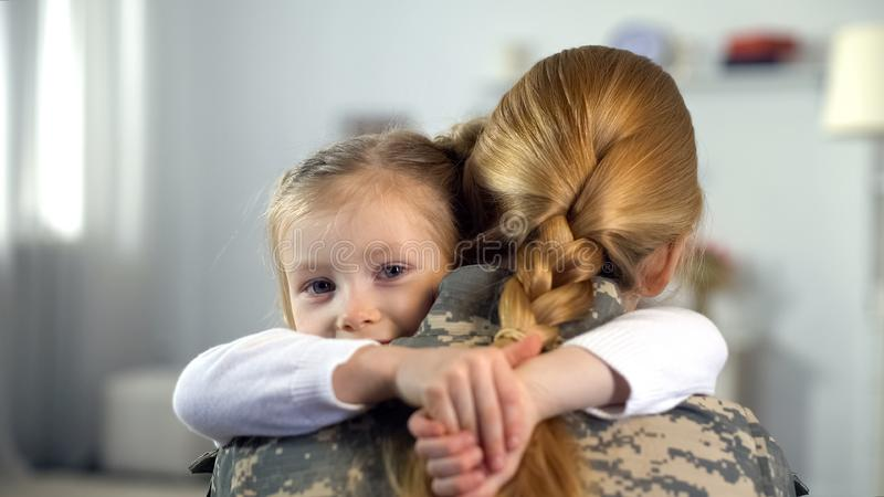 Little daughter hugging soldier mother in camouflage uniform, war homecoming royalty free stock photography